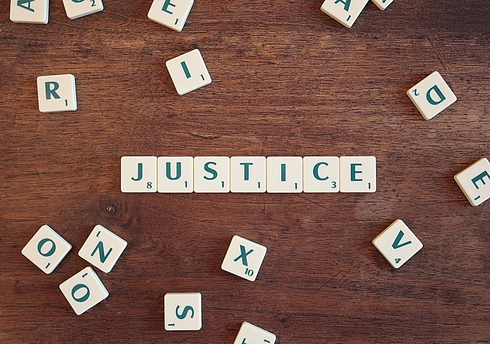"The word ""justice"" spelled in scrabble tiles"