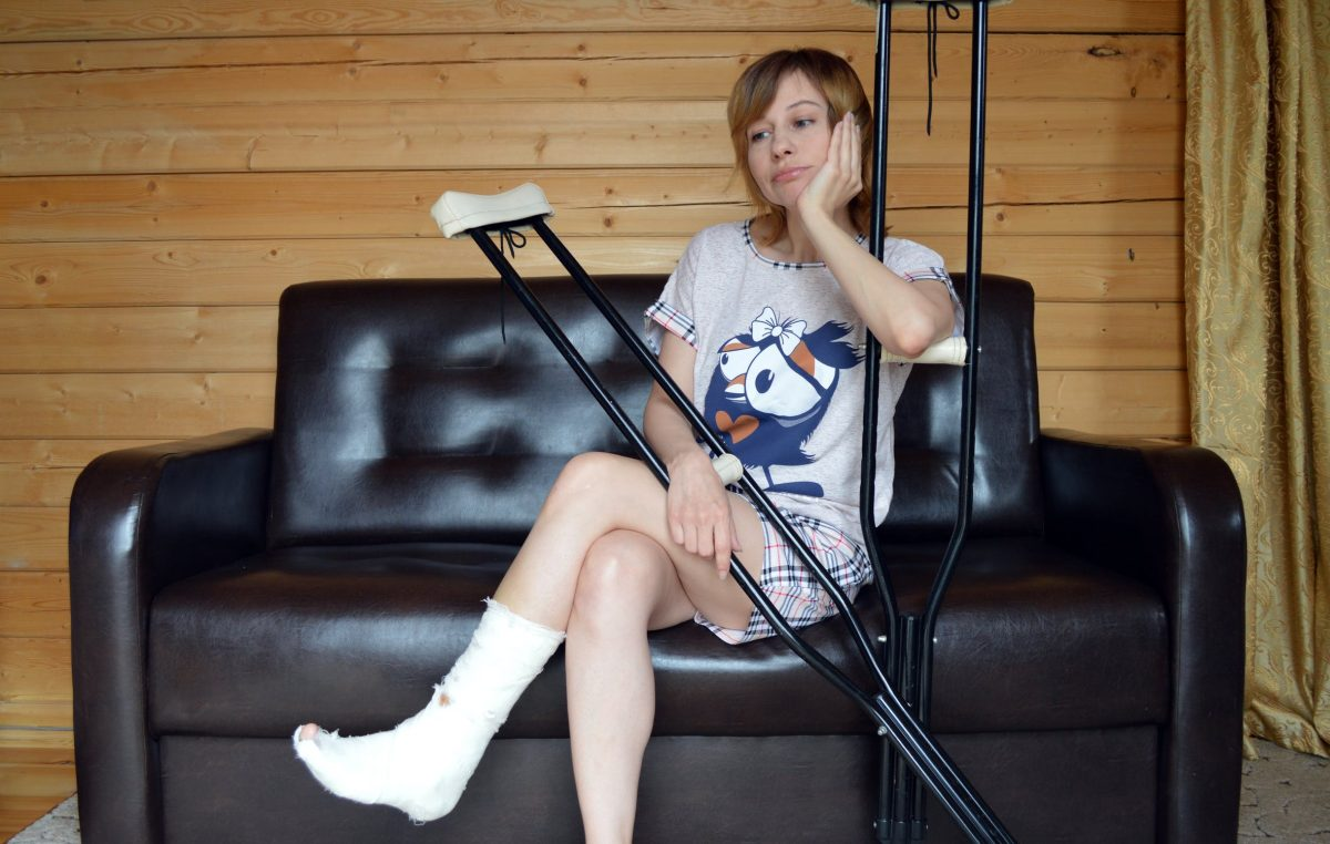 woman sitting down with crutches
