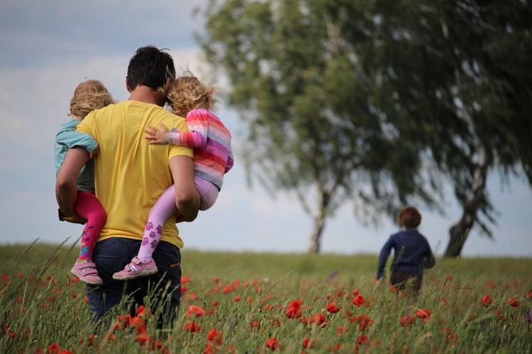 man carrying children through field